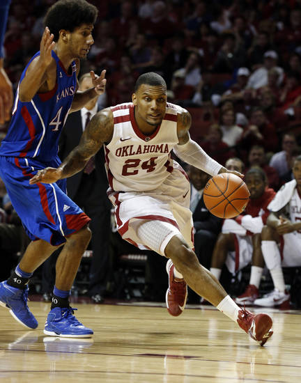 Oklahoma's Romero Osby (24) derives around Kansas' Kevin Young (40) during the second half as the University of Oklahoma Sooners (OU) defeat the Kansas Jayhawks (KU) 72-66 in NCAA, men's college basketball at The Lloyd Noble Center on Saturday, Feb. 9, 2013 in Norman, Okla. Photo by Steve Sisney, The Oklahoman