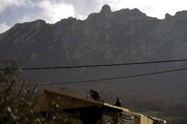 People work on a roof backdropped by the Pic de Bugarach mountain in the town of Bugarach, France, Thursday, Dec. 20, 2012. The clock is ticking down to Dec. 21, the supposed end of the Mayan calendar, and from China to California to Mexico, thousands are getting ready for what they think is going to be a fateful day. The sleepy town of Bugarach, nestled in the French Pyrenees mountains, is bracing for the arrival of hundreds of New Age enthusiasts and UFO believers that want to witness the end of the Mayan Long Count calendar. (AP Photo/Marko Drobnjakovic)