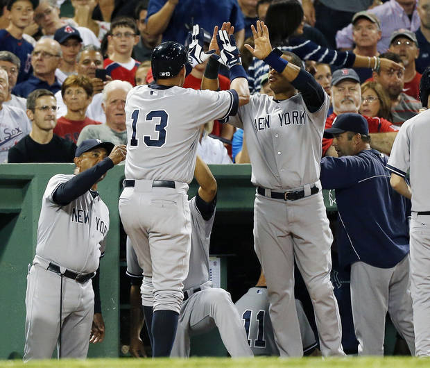 New York Yankees' Alex Rodriguez (13) celebrates with teammate Robinson Cano, center right, after scoring on a single by Eduardo Nunez in the second inning of a baseball game against the Boston Red Sox in Boston, Sunday, Aug. 18, 2013. (AP Photo/Michael Dwyer)