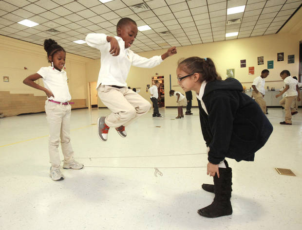 Sinaya Gaston, 7, left, Tyveon Moore, 7, and Angelina Echeverria, 8, jump rope Thursday in the old gym at Horace Mann Elementary School in Oklahoma City. Photo By Paul Hellstern, The Oklahoman