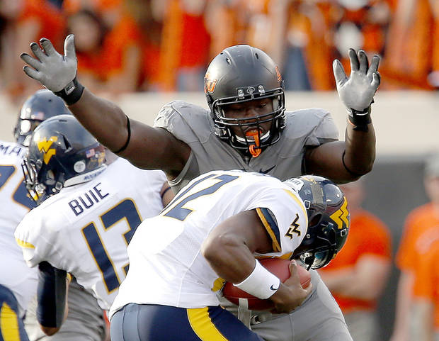 Oklahoma State's Anthony Rogers (94) pressures West Virginia's Geno Smith (12) during a college football game between Oklahoma State University (OSU) and the West Virginia University at Boone Pickens Stadium in Stillwater, Okla., Saturday, Nov. 10, 2012. OSU won 55-34. Photo by Sarah Phipps, The Oklahoman