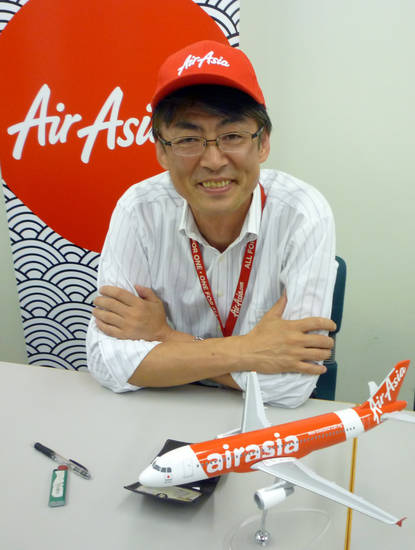 In this Sept. 28, 2012 photo, AirAsia Japan President Kazuyuki Iwakata smiles during an interview in Tokyo. �It�s not that the meals on standard fares were ever free. The charge was just part of the ticket price,� Iwakata told The Associated Press. �With us, people pay only for what they need.� As a marketing ploy, AirAsia Japan, which started operations in August, offered tickets for just 5 yen (5 cents) to the first 10,000 people. They quickly sold out. (AP Photo/Yuri Kageyama)