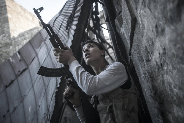 In this Saturday, Nov. 03, 2012 photo, a rebel fighter watches windows in an overlooking building as he awaits for loyalists to President Bashar Assad to appear during heavy fighting in the Jedida district of Aleppo, Syria.(AP Photo/Narciso Contreras)