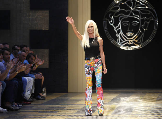 Italian fashion designer Donatella Versace waves as she receives applause from the audience, on the runway, after presenting Versace from the men's Spring-Summer 2013 collection, part of the Milan Fashion Week, unveiled in Milan, Italy, Saturday, June 23, 2012. (AP Photo/Luca Bruno)