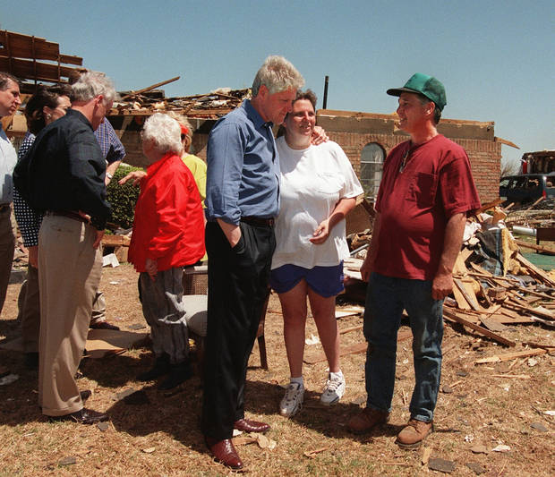 Tornado damage tour: President Bill Clinton with his arm around Tammy Weston speaks with she and her neighbor Harry Lindley.