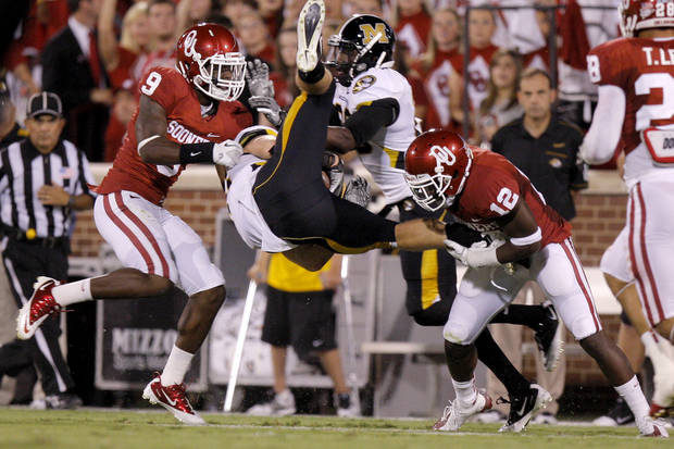 Oklahoma's Gabe Lynn and Javon Harris bring down Missouri's T.J. Moe during their game Saturday in Norman.  Photo by Bryan Terry, The Oklahoman