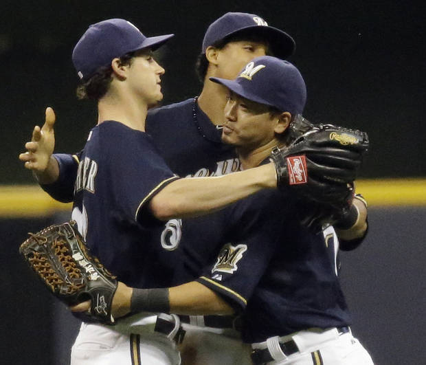 From left to right, Milwaukee Brewers' Logan Schafer, Carlos Gomez and Norichika Aoki celebrate after the ninth inning of a baseball game against the Atlanta Braves, Friday, June 21, 2013, in Milwaukee. The Brewers won 2-0. (AP Photo/Morry Gash)