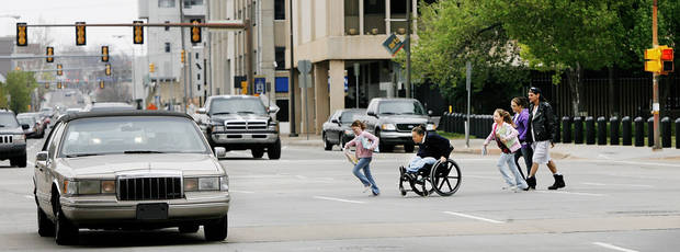 A woman in a wheelchair and children hurry to cross N. Hudson between the County Courthouse and City Hall in this 2009 photo. This photograph is actually of Hudson Ave but could easily be transposed onto E.K. Gaylord.