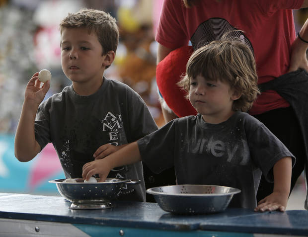 Brothers Gage Woodard, 6, and Crue Woodard, 3, play a game Sunday at the Oklahoma State Fair in Oklahoma City. Photos by Garett Fisbeck, The Oklahoman