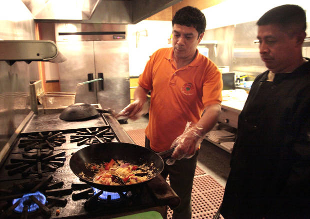 Ceviche House owner Juan Castro, left, shows Damian Gonzales how it's done. <strong>SARAH PHIPPS - THE OKLAHOMAN</strong>