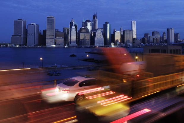 Early morning traffic in New York's Brooklyn borough moves slowly beneath the Manhattan skyline, Thursday, Nov. 1, 2012. New York is trying to resume its normal frenetic pace Thursday, getting back its vital subway system, but still finding it slow going on gridlocked highways. (AP Photo/Mark Lennihan)