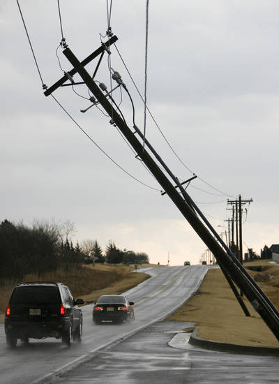 Cars drive past a leaning utility line on Covell in Edmond, Okla., after a storm, Tuesday, Feb. 10, 2009. PHOTO BY BRYAN TERRY, THE OKLAHOMAN