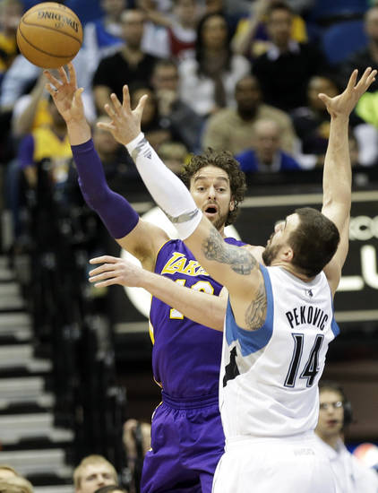 Los Angeles Lakers' Pau Gasol, left, of Spain, sends a pass over Minnesota Timberwolves' Nikola Pekovic, of Montenegro, in the first quarter of an NBA basketball game, Friday, Feb. 1, 2013, in Minneapolis. (AP Photo/Jim Mone)