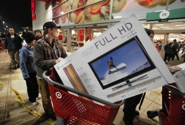 Ryan Martin pushes his door buster purchase from the store after Target's midnight opening on Black Friday, Nov. 25, 2011, in Moore, Okla. Photo by Steve Sisney