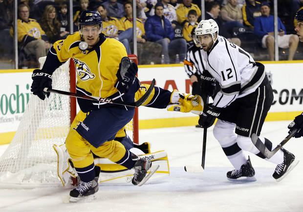 Nashville Predators defenseman Roman Josi (59), of Switzerland, tries to grab a loose puck as he chases it with Los Angeles Kings left wing Simon Gagne (12) in the first period of an NHL hockey game, Thursday, Feb. 7, 2013, in Nashville, Tenn. (AP Photo/Mark Humphrey)