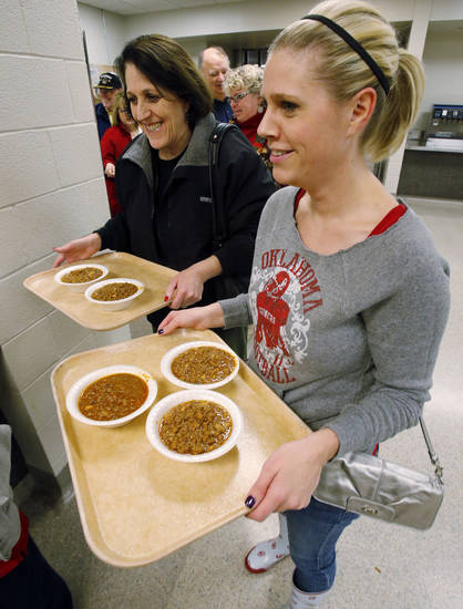 Above: Linda Holt and Jenni Grissom carry trays of chili.  PHOTOS BY STEVE SISNEY,  THE OKLAHOMAN