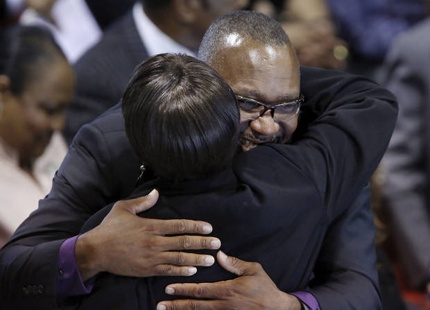 Joe Carter, Jr., is hugged at the end of the funeral as ministers greet each member of Joe Carter Sr.'s family. About 400 family and friends gathered inside the Millwood High School Fieldhouse on  Tuesday,  Sep, 25, 2012, to honor the life and say farewell to Joseph D. Carter, Sr. at a funeral service that was sentimental and touching, but also full of joy and laughter. Carter is survived by a wife and their 11 children as well as 46 grandchildren, 35 great-grandchildren and 10 great-great-grandchildren. Photo by Jim Beckel, The Oklahoman.