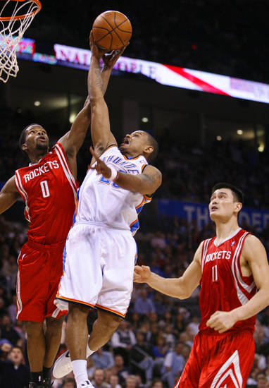 Earl Watson takes a steal to the basket and is fouled by Aaron Brooks (0) in the second half as the Oklahoma City Thunder plays the Houston Rockets at the Ford Center in Oklahoma City, Okla. on Friday, January 9, 2009. 