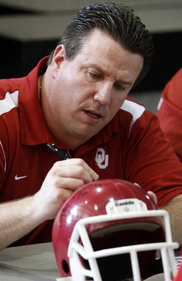 Bill Bedenbaugh, offensive line coach, signs autographs during fan appreciation day for the University of Oklahoma Sooner (OU) football team at Gaylord Family-Oklahoma Memorial Stadium in Norman, Okla., on Saturday, Aug. 3, 2013. Photo by Steve Sisney, The Oklahoman