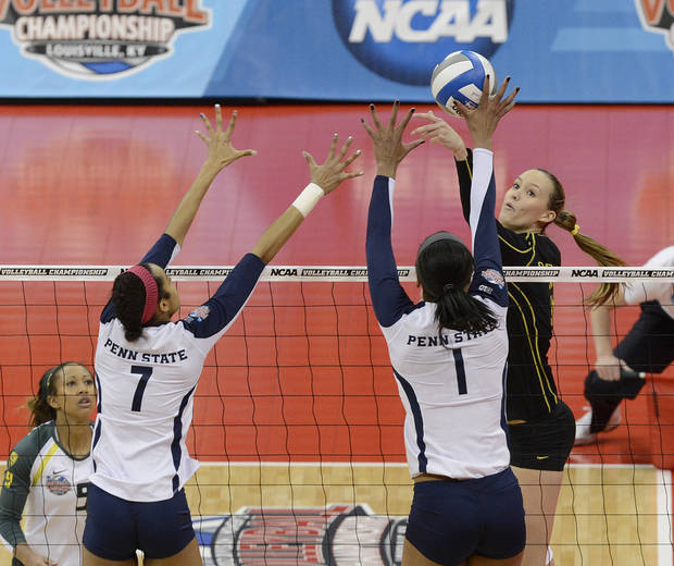 Oregon's Alaina Bergsma, facing, attempts to hit over the defense of Penn State's Nia Grant, left, and Ariel Scott during the national semifinals of the NCAA college women's volleyball tournament Thursday, Dec. 13, 2012 in Louisville, Ky. (AP Photo/Timothy D. Easley)