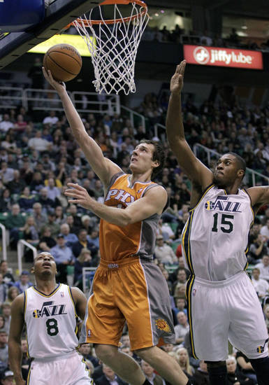 Phoenix Suns point guard Goran Dragic, center, of Slovenia, lays the ball up as Utah Jazz power forward Derrick Favors (15) defends in the first quarter during an NBA basketball game on Saturday, Nov. 10, 2012, in Salt Lake City. (AP Photo/Rick Bowmer)