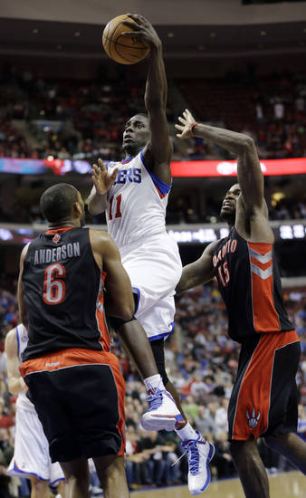Philadelphia 76ers' Jrue Holiday, center, shoots between Toronto Raptors' Alan Anderson, left, and Amir Johnson in overtime of an NBA basketball game on Friday, Jan. 18, 2013, in Philadelphia. Philadelphia won 108-101. (AP Photo/Matt Slocum)