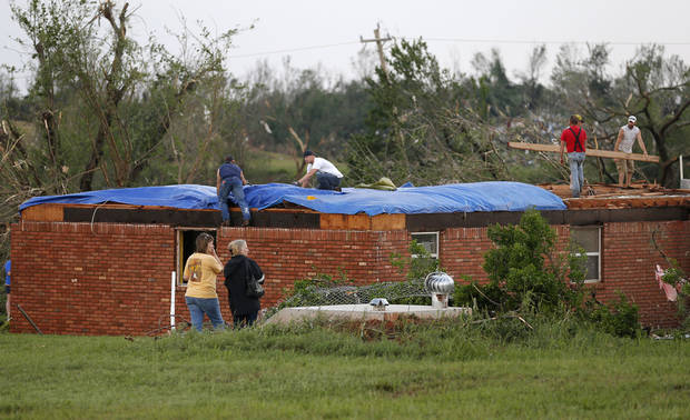 People work to cover a home that was damaged by a tornado in Carney Okla., on Sunday, May 19, 2013. Photo by Bryan Terry, The Oklahoman