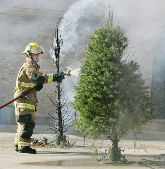 CHRISTMAS TREE FIRE SAFETY: The unwatered real tree to the left and a regularly watered one are hosed down by Station 4 firefighter Chad Wilds after a demonstration by OKC firefighters on Thursday, Dec. 11, 2008 in OKC. THE OKLAHOMAN ARCHIVES <strong>Jaconna Aguirre - THE OKLAHOMAN</strong>