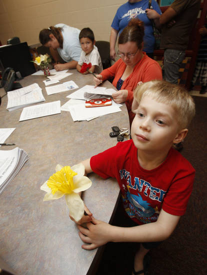 Chase Noon, 5, waits for his mom Delilah Coffman to fill out paperwork Monday during enrollment for the 2012-13 school year at Cesar Chavez Elementary School in Oklahoma City. <strong>PAUL HELLSTERN - THE OKLAHOMAN</strong>
