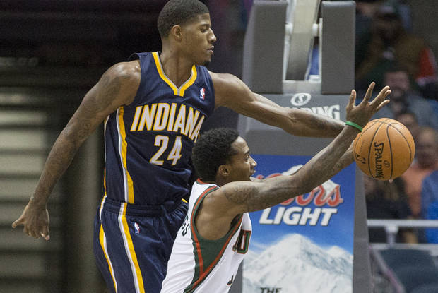 Indiana Pacers' Paul George , left, blocks a shot-attempt by Milwaukee Bucks' Brandon Jennings during the second half of an NBA basketball game on Wednesday, Nov. 14, 2012, in Milwaukee. (AP Photo/Tom Lynn)