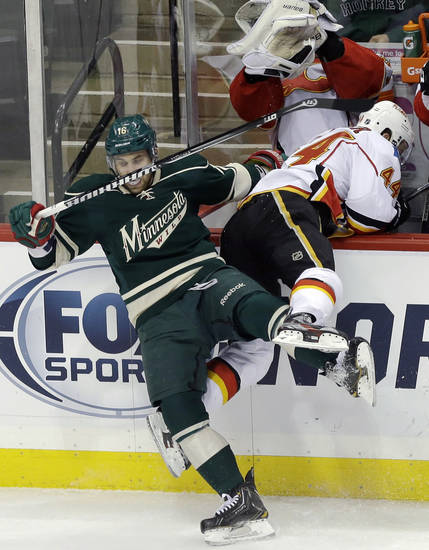 Calgary Flames' Chris Butler, right, winds up partly in his team's bench courtesy of Minnesota Wild's Jason Zucker in the first period of an NHL hockey game on Sunday, April 21, 2013, in St. Paul, Minn. (AP Photo/Jim Mone)