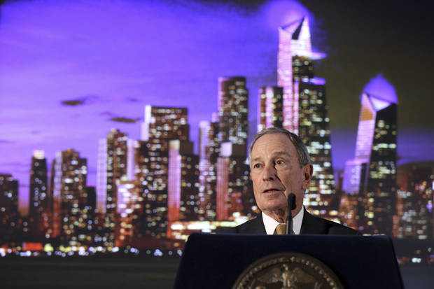 New York City Mayor Michael Bloomberg stands by by an artist's rendering of  a new neighborhood called Hudson Yards as he speaks during the ground breaking ceremony, Tuesday, Dec. 4, 2012 in New York. The 26-acre site on Manhattan's west side is the planned home for a new business district.  Those connected to the Hudson Yards plan envision millions of square feet of office space and housing, as well as a riverfront park and a cultural center.  (AP Photo/Mary Altaffer)