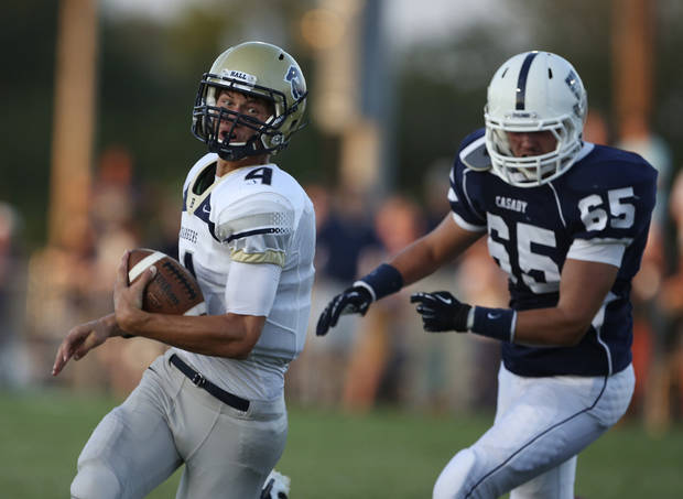 Heritage Hall's Connor McGinnis (4) runs from Casady's Blake Gunn (65) during a game at Casady High School in The Village, Okla., Thursday, Aug. 30, 2012.  Photo by Garett Fisbeck, The Oklahoman