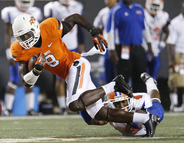 Oklahoma State's C.J Curry is tripped up by Savannah State's John Wilson (4)  during a college football game between Oklahoma State University (OSU) and Savannah State University at Boone Pickens Stadium in Stillwater, Okla., Saturday, Sept. 1, 2012. Photo by Sarah Phipps, The Oklahoman
