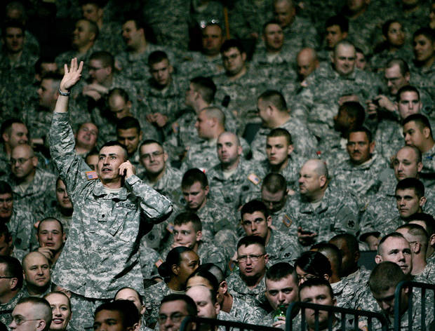 John Pino waves to his family in the audience and talks with them on the phone before a deployment ceremony for members of the 45th Infantry Brigade Combat Team at The OKC Arena in Oklahoma City on Wednesday, Feb. 16, 2011. Photo by John Clanton, The Oklahoman
