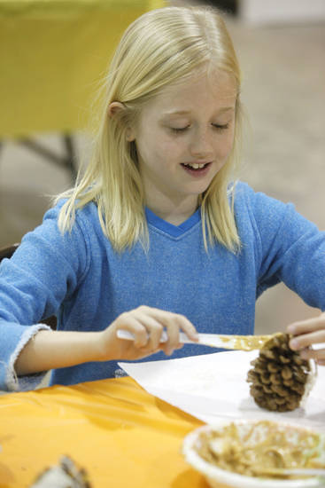Quin Freeny, 9, spreads peanut butter on a pine cone.