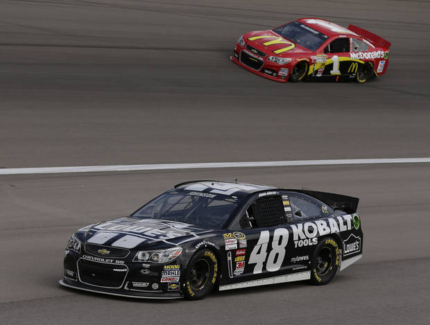 Jimmie Johnson (48) pulls off the track and heads back to the garage as Jamie McMurray (1) comes out of turn four during practice for the NASCAR Sprint Cup Series race, Saturday, March 9, 2013 in Las Vegas. (AP Photo/Julie Jacobson)