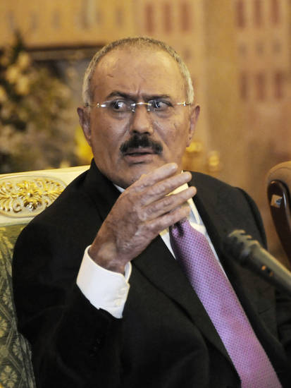 FILE - In this Saturday, Dec. 24, 2011 file photo, Yemen's President Ali Abdullah Saleh speaks to reporters during a press conference at the Presidential Palace in Sanaa, Yemen. Gunmen loyal to Yemen's ousted president blasted buildings at the country's main airport with anti-aircraft guns on Saturday, forcing authorities to shut it down, an airport official said. The attack comes a day after Yemen's new President Abed Rabbo Mansour Hadi fired key security officials appointed by ex-president Ali Abdullah Saleh including his half brother, the air force commander Mohammed Saleh al-Ahmar, and his nephew, Tariq, who headed the presidential guard. (AP Photo/Mohammed Hamoud, File)