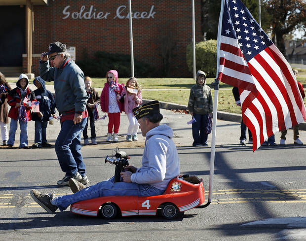 Members of VFW Post 7192 entertained people at the parade with a miniature go-cart. The city of Midwest City teamed with civic leaders and local merchants to display their appreciation for veterans and active military forces by staging a hour-long Veteran&#039;s Day parade that stretched more than a mile and a half along three of the city&#039;s busiest streets Monday morning, Nov. 12, 2012. Hundreds of people lined the parade route, many of them waving small American flags that had ben distributed by volunteers who marched near the front of the parade. A fly-over performed by F-16s from the138th Fighter Wing, Oklahoma Air National Guard unit in Tulsa thrilled spectators. Five veterans representing military personnel who served in five wars and military actions served as  Grand Marshals for the parade. Leading the parade was the Naval Reserve seven-story American flag, carried by 100 volunteers from First National Bank of Midwest City, Advantage Bank and the Tinker Federal Credit Union. The flag is 50 feet by 76 feet, weighs 110 pounds and was sponsored by the MWC Chapter of Disabled American Veterans. Photo by Jim Beckel, The Oklahoman