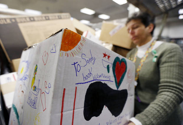 Cathy Zieff, postmaster at the Newtown, Conn., post office, holds a package sent to the families of the victims of the Sandy Hook Elementary School shooting, Friday, Dec. 21, 2012, in Newtown, Conn. (AP Photo/Julio Cortez)