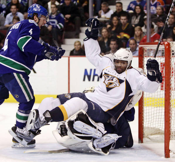 Nashville Predators' Joel Ward, right, falls on Vancouver Canucks' goalie Roberto Luongo as Canucks' Keith Ballard, left, watches during the first period of an NHL hockey game in Vancouver, British Columbia, on Wednesday, Jan. 26, 2011. (AP Photo/The Canadian Press, Darryl Dyck)