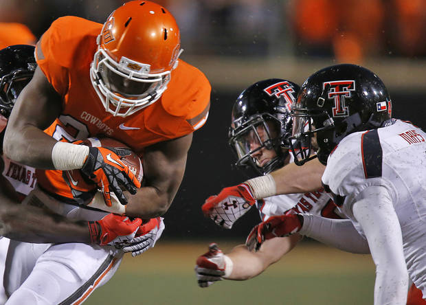 Oklahoma State&#039;s Desmond Roland (26) runs through the Tech defense during the college football game between the Oklahoma State University Cowboys (OSU) and Texas Tech University Red Raiders (TTU) at Boone Pickens Stadium on Saturday, Nov. 17, 2012, in Stillwater, Okla.   Photo by Chris Landsberger, The Oklahoman