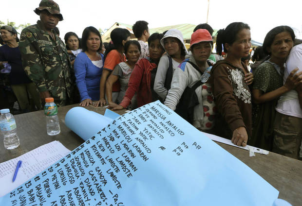 A list of missing residents is prepared to be posted on a wall as residents, impacted by Tuesday's typhoon,  line up for relief supplies Thursday, Dec. 6, 2012, in New Bataan township, Compostela Valley in the southern Philippines.  The powerful typhoon that washed away emergency shelters, a military camp and possibly entire families in the southern Philippines has killed hundreds of people with nearly 400 missing, authorities said Thursday. (AP Photo/Bullit Marquez)