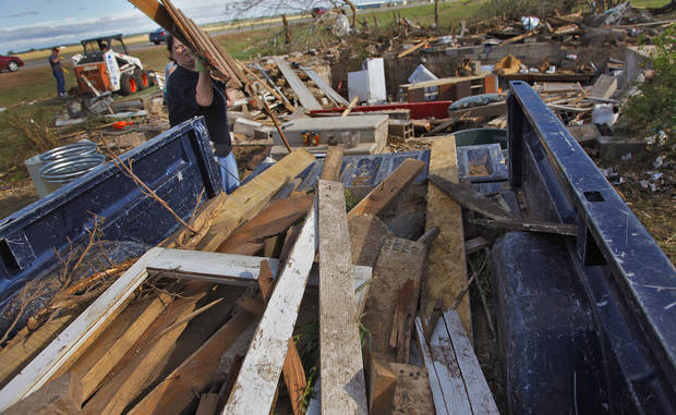 Angie Dean helps clean the damage at the home of Tom Chronister that was destroyed by Tuesday's tornado north of El Reno, Wednesday, May 25, 2011. Photo by Chris Landsberger, The Oklahoman