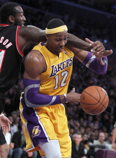 Portland Trail Blazers center J.J. Hickson, left, battles Los Angeles Lakers center Dwight Howard (12) for a loose ball during the first quarter of an NBA basketball game, Friday, Dec. 28, 2012, in Los Angeles.  (AP Photo/Alex Gallardo)