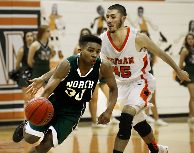 Norman North's Najji Brown goes around Jay Finley as the Norman High School Tigers play the Norman North Timberwolves on Friday, Feb. 15, 2013  in Norman, Okla. Photo by Steve Sisney, The Oklahoman