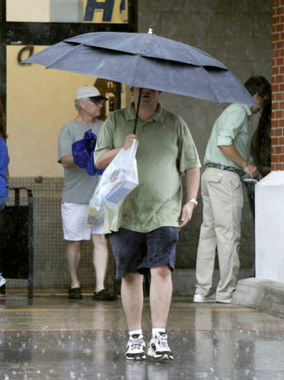 A shopper walks through a heavy rain as he leaves the Homeland store on North May Ave. and Britton Road in Oklahoma City, OK, Saturday, August 18, 2012,  By Paul Hellstern, The Oklahoman