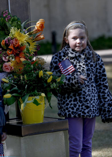 Kamryn Kuhlman holds an American Flag as she stands beside the chair of bombing victim Shelly Brand during the 18th Anniversary Remembrance Ceremony of the Oklahoma City bombing on Friday, April 19, 2013, in Oklahoma City, Okla.   Photo by Chris Landsberger, The Oklahoman