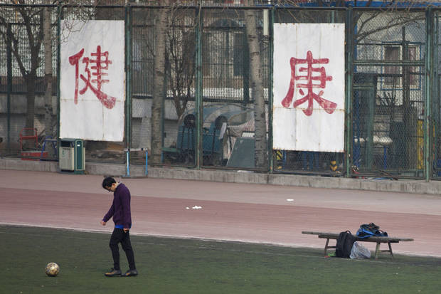 "In this Saturday, Jan. 19, 2013 photo. a college student kicks a soccer ball in front of Chinese characters on the fence reading ""good health"" in Beijing. Despite its formidable performance in recent Olympic Games, China has found itself in a crisis of declining fitness among its youngsters. (AP Photo/Alexander F. Yuan)"