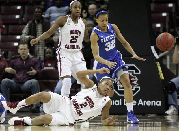 Kentucky's Kastine Evans (32) goes for the loose ball as South Carolina's Ieasia Walker (2) falls to the court and Tiffany Mitchell (25) watches during the first half of their NCAA college basketball game, Thursday, Jan. 24, 2013, in Columbia, S.C. (AP Photo/Mary Ann Chastain)